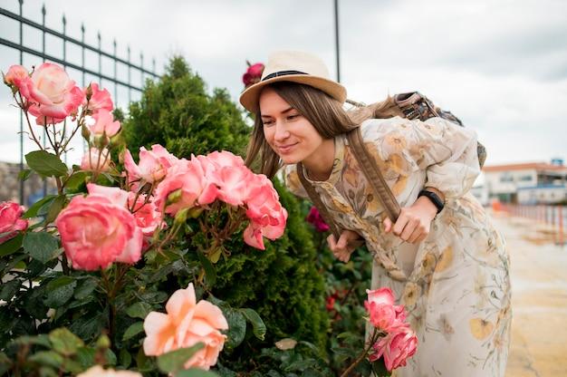 Portret van mooie vrouw met hoed ruikende bloemen