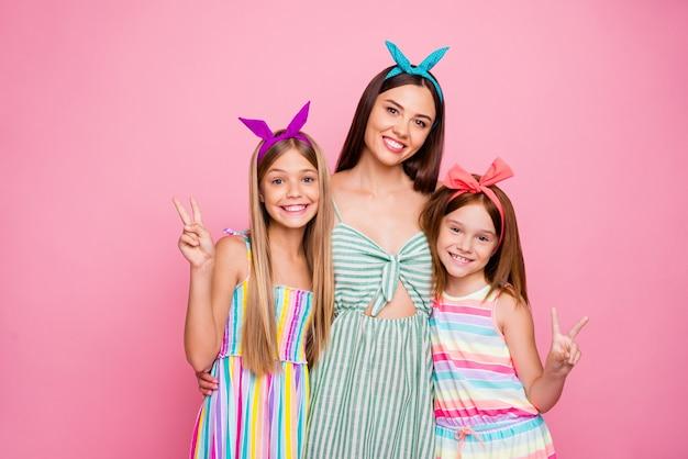 Portret van mooie vrouw met hoofdband die haar twee kinderen knuffelen die v-tekens maken die lichte kledingrok dragen die over roze achtergrond wordt geïsoleerd