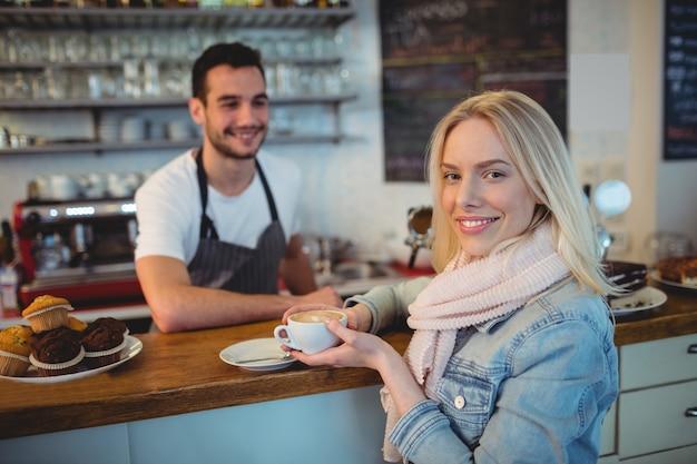 Portret van mooie vrouw met kelner bij koffie