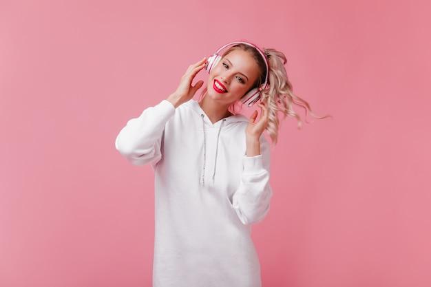 Portret van mooie vrouw met krullende paardenstaart in hoofdtelefoons op geïsoleerde muur