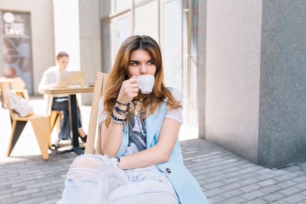 Portret van mooie vrouw met lang haar, zittend op een stoel in café buiten