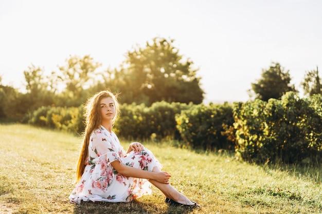 Portret van mooie vrouw met lang krullend haar op bes veld. het meisje in een lichte kleding zit op het gras in zonnige dag