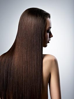 Portret van mooie vrouw met lang recht bruin haar in de studio