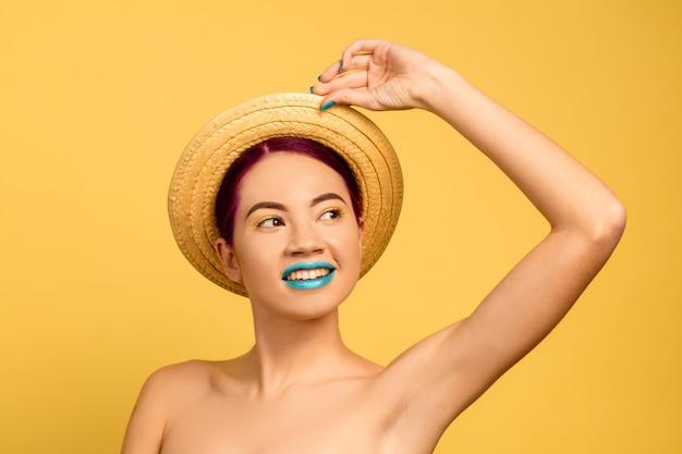 Portret van mooie vrouw met lichte make-up en hoed op gele studio