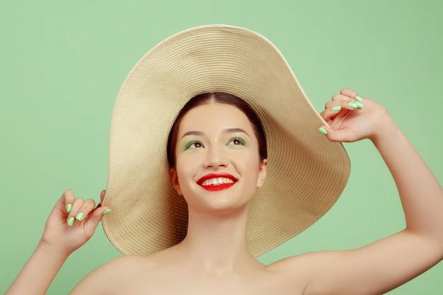 Portret van mooie vrouw met lichte make-up en hoed op groene studio