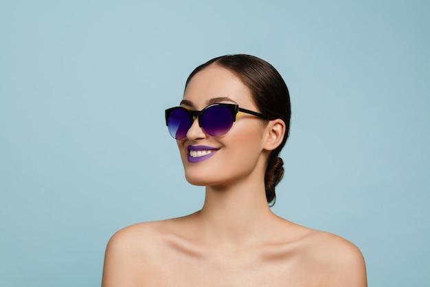 Portret van mooie vrouw met lichte make-up en zonnebril op blauwe studioachtergrond. stijlvol, modieus merk en kapsel. kleuren van de zomer. schoonheid, mode en advertentieconcept. lachend.
