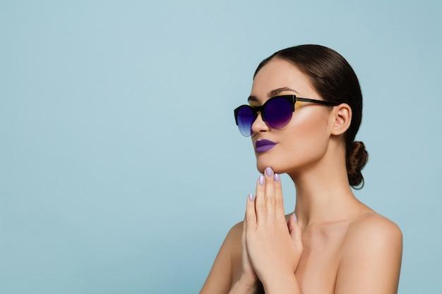 Portret van mooie vrouw met lichte make-up en zonnebril. stijlvol, modieus merk en kapsel. kleuren van de zomer. serieus, zelfverzekerd.