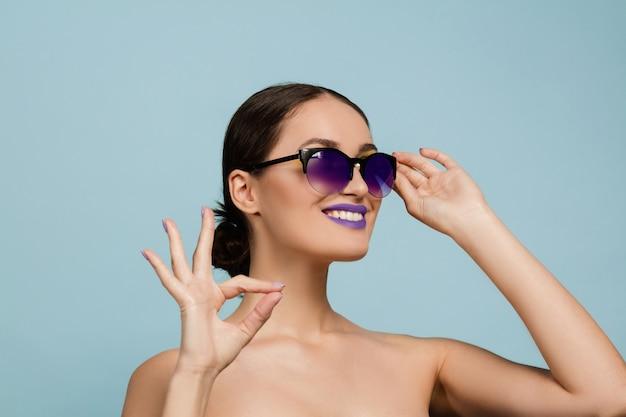 Portret van mooie vrouw met lichte make-up en zonnebril. stijlvol, modieus merk en kapsel. kleuren van de zomer. toont teken van aardig.