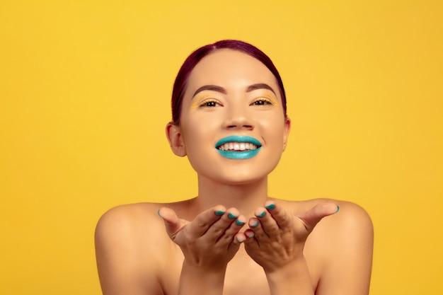 Portret van mooie vrouw met lichte make-up, haar en manicure op gele studio