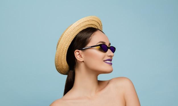 Portret van mooie vrouw met lichte make-up, hoed en zonnebril op blauwe studio