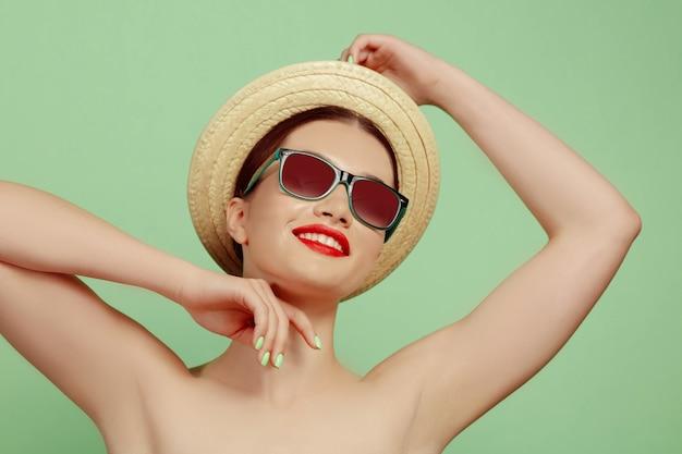 Portret van mooie vrouw met lichte make-up, hoed en zonnebril op groene studio