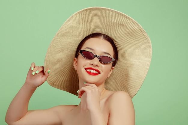 Portret van mooie vrouw met lichte make-up, hoed en zonnebril op groene studioachtergrond. stijlvol en modieus merk en kapsel. kleuren van de zomer. schoonheid, mode en advertentieconcept. lachend.