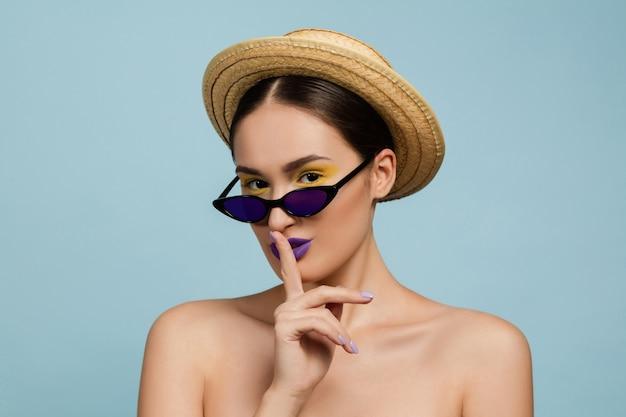 Portret van mooie vrouw met lichte make-up, hoed en zonnebril. stijlvol en modieus merk en kapsel. kleuren van de zomer. geheim.