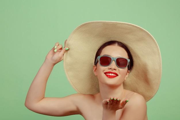 Portret van mooie vrouw met lichte make-up, rode brillen en hoed op groene ruimte. stijlvol en modieus merk, kapsel. schoonheid, mode en advertentieconcept