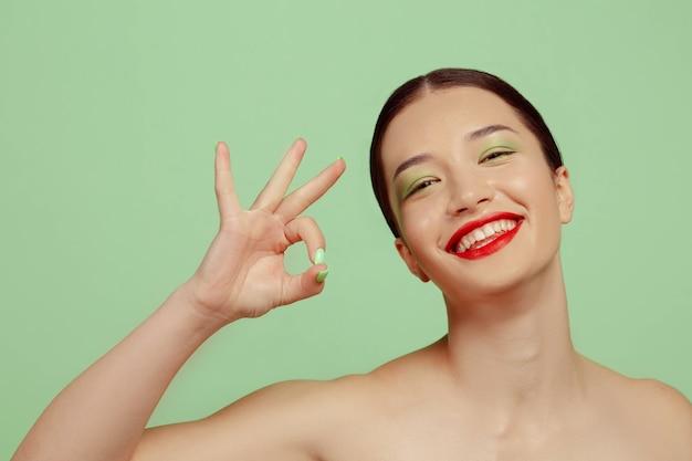 Portret van mooie vrouw met lichte make-up, rode brillen en hoed op groene ruimte. stijlvol en modieus merk, kapsel