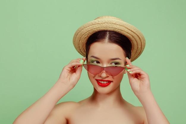Portret van mooie vrouw met lichte make-up, rode brillen en hoed op groene studio