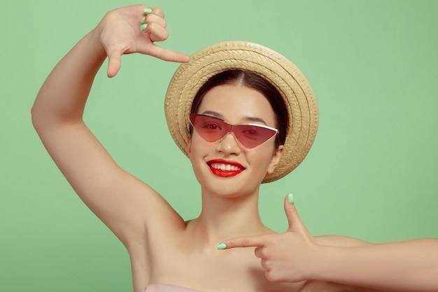 Portret van mooie vrouw met lichte make-up, rode brillen en hoed op groene studioachtergrond. stijlvol en modieus merk, kapsel. schoonheid, mode en advertentieconcept. glimlachen, een schot maken.