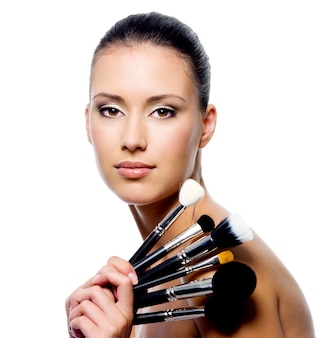 Portret van mooie vrouw met make-upborstels - die op wit wordt geïsoleerd