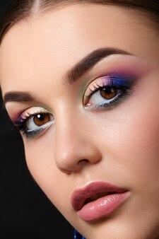 Portret van mooie vrouw met maniermake-up die blauwe oorringen draagt. moderne maniermake-up. veelkleurige smokey eyes.