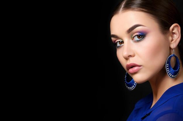 Portret van mooie vrouw met maniermake-up die blauwe oorringen draagt