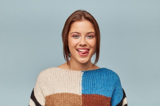 Portret van mooie vrouw met modern kapsel likken bovenlip met tong uit
