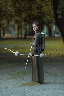 Portret van mooie vrouw met oude pijlkoker met pijlen en boog