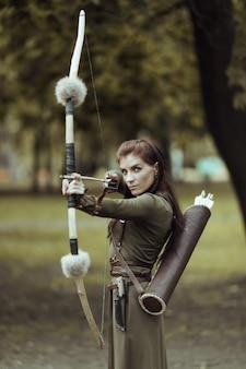Portret van mooie vrouw met pijlen en boog, gericht op doel