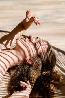 Portret van mooie vrouw met schaduwen van palmblad op haar gezicht. concept van zonnebaden, vakantie.