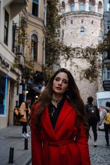 Portret van mooie vrouw met uitzicht op de galata-toren in istanbul, turkije. reizen en vakantie in turkije concept