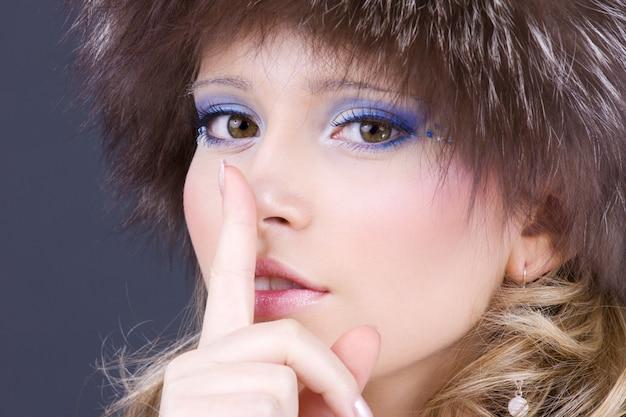 Portret van mooie vrouw met vinger op lippen