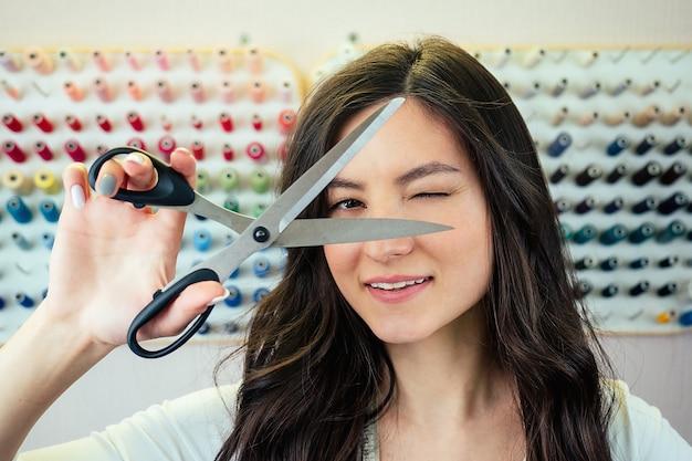 Portret van mooie vrouw naaister bedrijf schaar. de kleermaker poseert bij een lichte muur. naaister, schaar, meetlint en draad in de werkplaats.