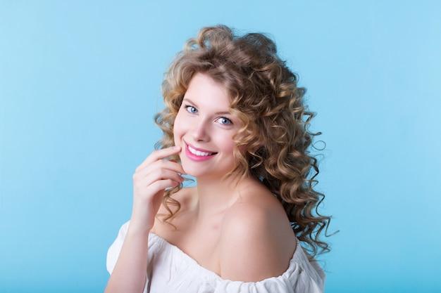 Portret van mooie vrouw op een blauwe muur.