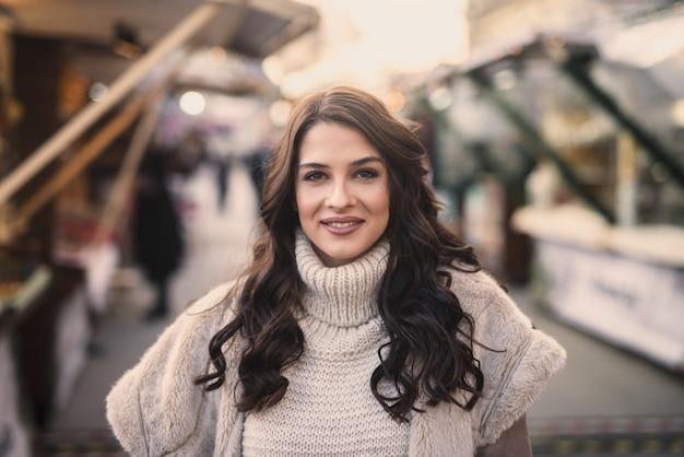 Portret van mooie vrouw op straat staan en glimlachen.
