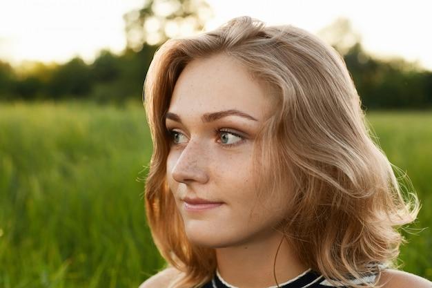 Portret van mooie vrouw over groen park