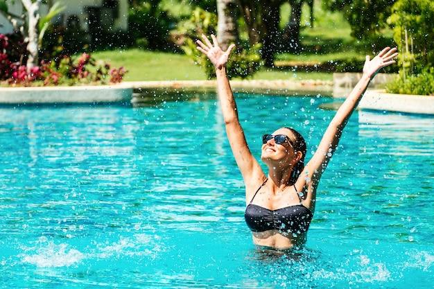 Portret van mooie vrouw permanent in zwembad met opgeheven armen