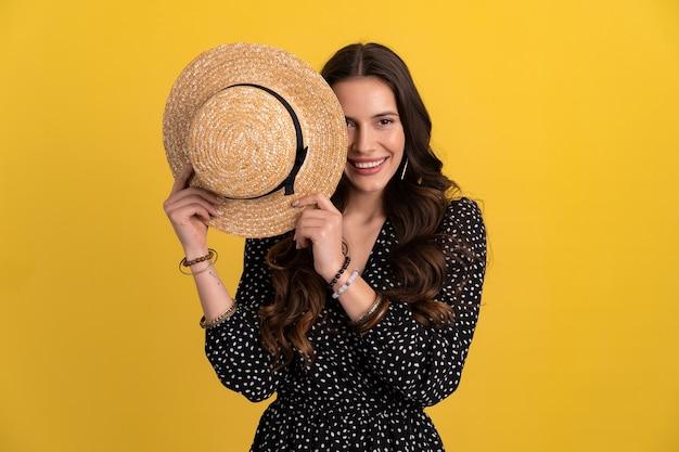 Portret van mooie vrouw poseren geïsoleerd op geel met zwarte gestippelde jurk en strohoed stijlvolle boho trend