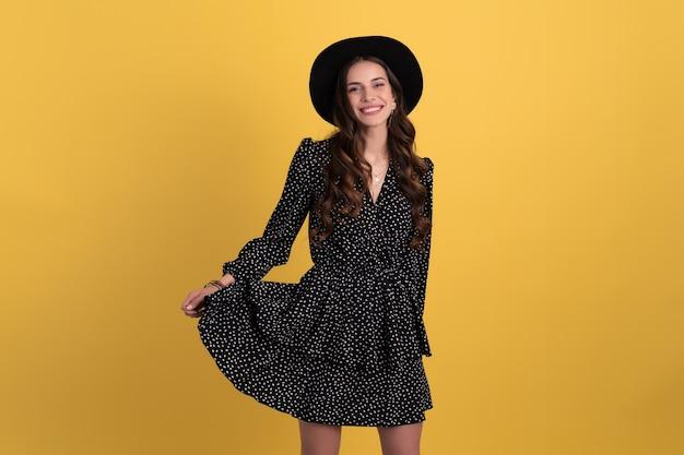 Portret van mooie vrouw poseren geïsoleerd op geel met zwarte gestippelde jurk en zwarte hoed