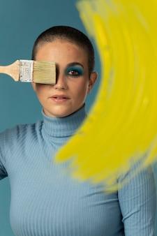 Portret van mooie vrouw poseren in een coltrui met gele verf penseelstreek