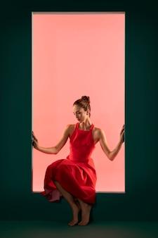 Portret van mooie vrouw poseren met een zwierige rode jurk
