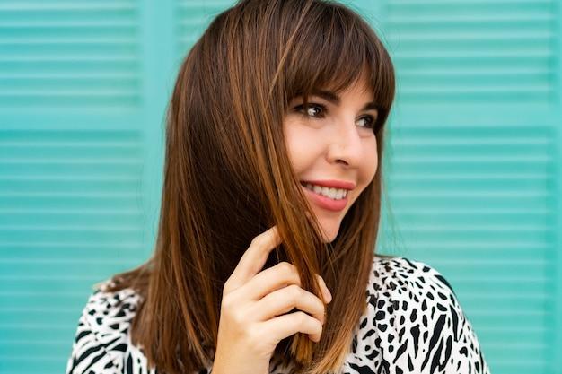 Portret van mooie vrouw poseren over blauwe muur close-up.
