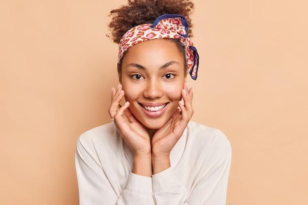 Portret van mooie vrouw raakt gezicht zachtjes glimlacht breed heeft perfecte witte tanden draagt hoofdband en shirt kijkt vrolijk naar voren geïsoleerd over beige muur