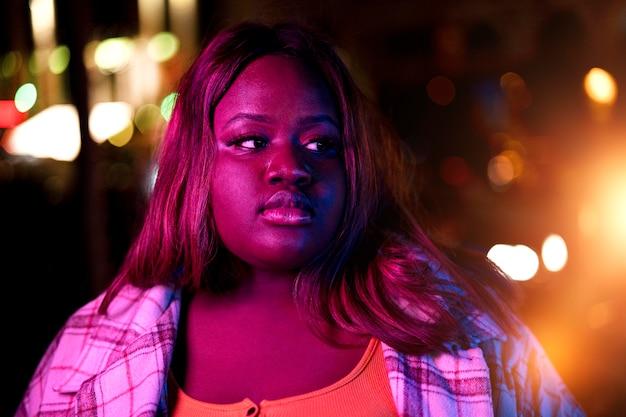 Portret van mooie vrouw 's nachts in de stadslichten