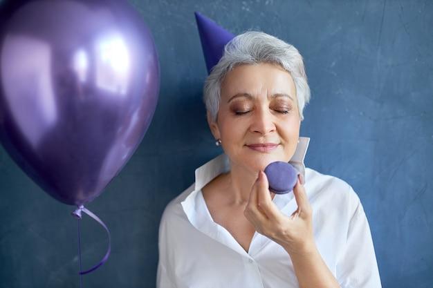 Portret van mooie vrouw van middelbare leeftijd in wit overhemd en kegelhoed ogen sluiten met plezier, anticiperend op zoete smaak