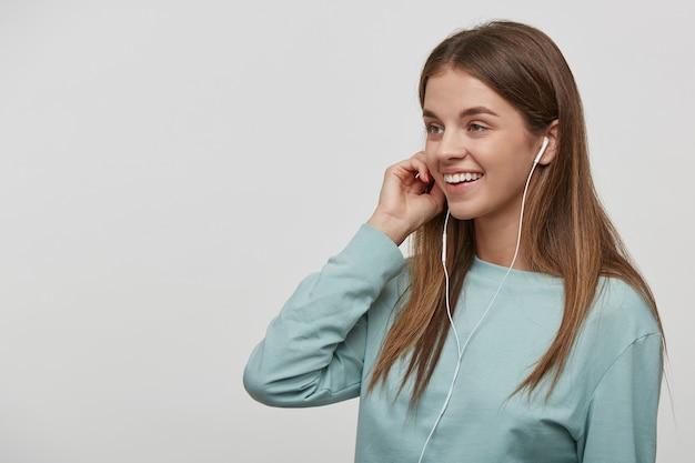 Portret van mooie vrouw vreugdevolle luisteren naar muziek op de mobiele telefoon, glimlachend