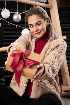Portret van mooie vrouw zitten en het geven van een kerstcadeau