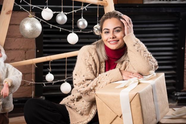 Portret van mooie vrouw zitten met kerstcadeautjes