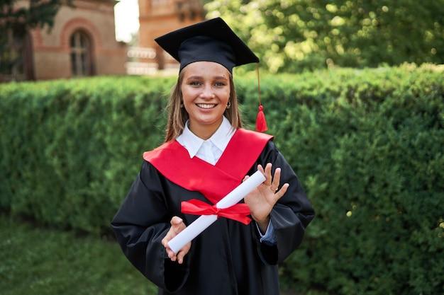 Portret van mooie vrouwelijke afgestudeerde in afstuderen gowm met diploma camera kijken.