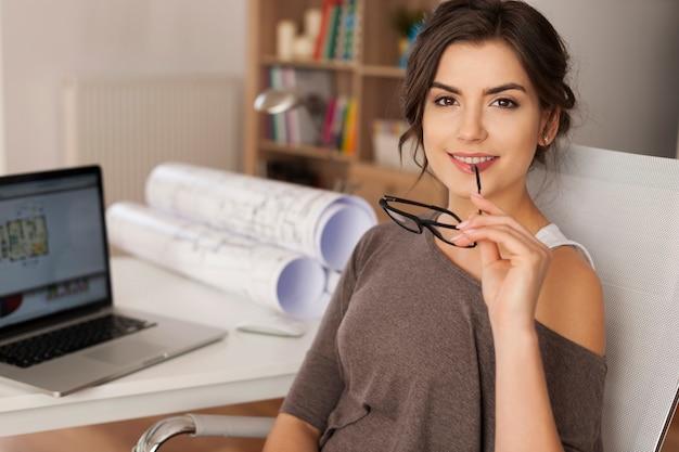 Portret van mooie vrouwelijke architect in plaats van werk