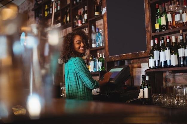 Portret van mooie vrouwelijke barman met behulp van elektronische machine