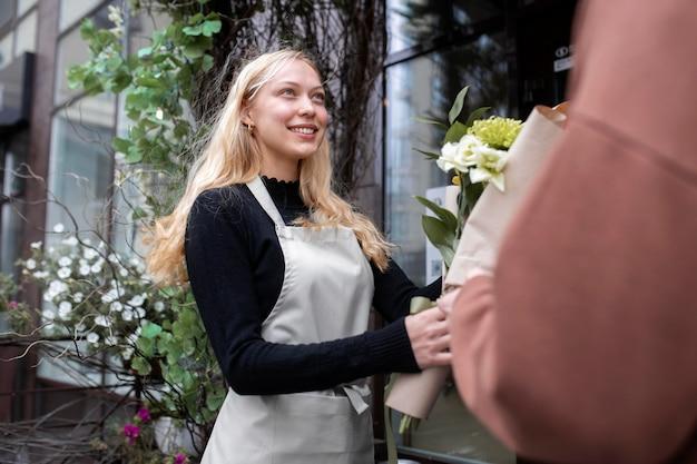 Portret van mooie vrouwelijke bloemist op het werk